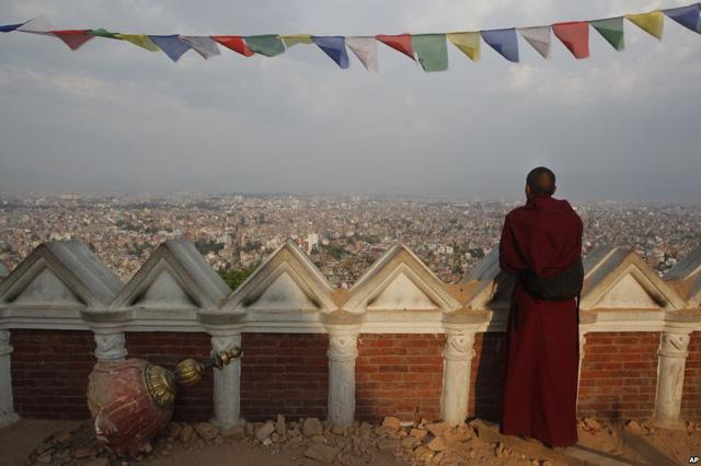 Nhà sư quan sát toàn cảnh thành phố Kathmandu từ tòa tháp Swayambhunath Stupa bị phá hủy trong trận động đất mới đây ở Kathmandu, Nepal.