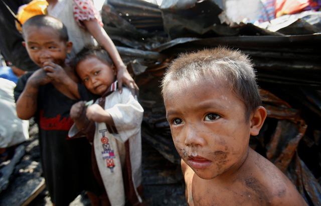 Trẻ em đứng chờ bên ngoài một ngôi nhà bị cháy rụi sau một vụ hỏa hoạn lớn tại Manila, Philippines.