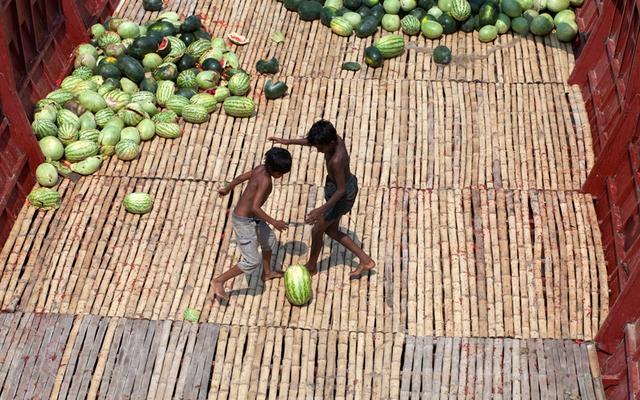 Trẻ chơi đá bóng bằng một quả dưa hấu trên một tàu vận tải dưới sông Buriganga, Bangladesh.