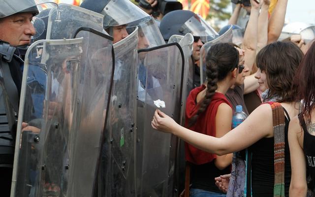 Cô gái tặng hoa cho cảnh sát đứng bảo vệ trước tòa nhà chính phủ ở Skopje, Macedonia.
