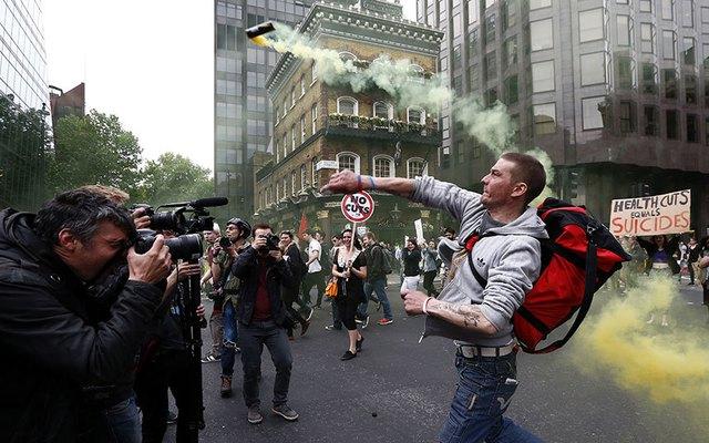 Người biểu tình ném lựu đạn khói trong cuộc biểu tình chống chính sách khắc khổ bên ngoài tòa nhà quốc hội ở London, Anh.