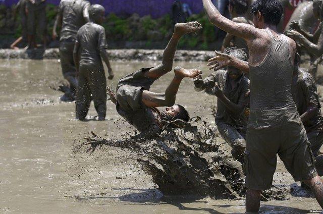 Cậu bé bị ném xuống bùn trong lễ hội xuống đồng Asar Pandhra tại thung lũng Pokhara ở thủ đô Kathmandu, Nepal.