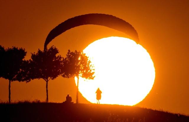 Một người chơi dù lượt đáp xuống đất khi mặt trời lặn ở Hannover, Đức.