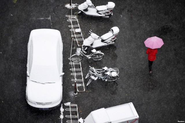 Người phụ nữ cầm ô trong khi đi dưới mưa tuyết tại thành phố Bắc Kinh, Trung Quốc.