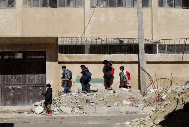 Trẻ em đi qua đống đổ nát trên đường phố ở Idlib, Syria.