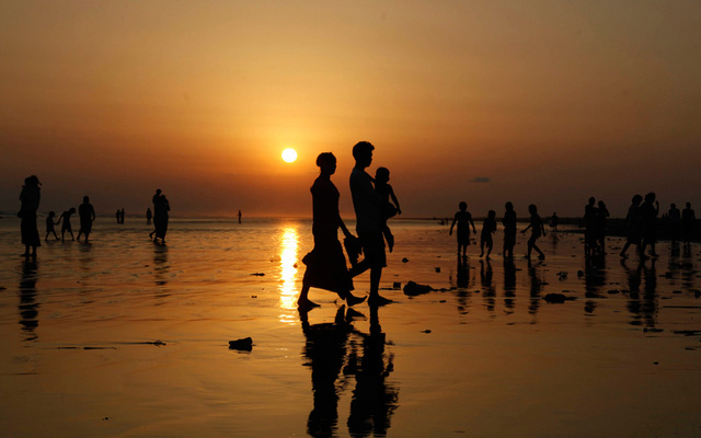 Mọi người dạo chơi trên bãi biển khi hoàng hôn xuống ở Sittwe, tây Myanmar.