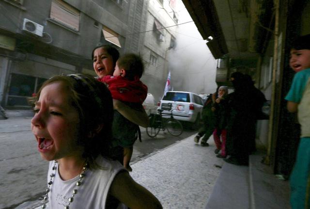 Trẻ em chạy trốn khỏi một vụ nã pháo nhằm vào thành phố Damascus, Syria.