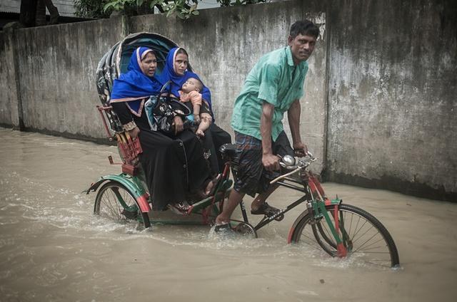 Người đàn ông đạp xe ba bánh chở khách qua đoạn đường ngập nước ở Chittagong, Bangladesh.