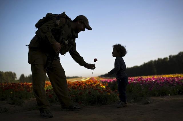Binh sĩ Israel tặng hoa cho một em bé trên cánh đống gần Kibbutz Nir Yitzhak, miền nam Israel.