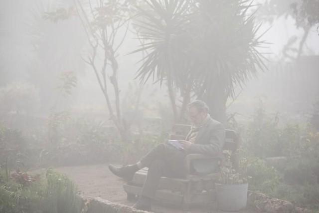 Người đàn ông ngồi đọc sách trong màn sương mù dày đặc bao phủ Cairo, Ai Cập.