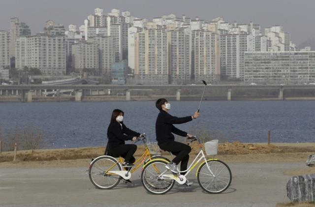 Người dân đeo khẩu trang đi xe đạp sau khi chính quyền thành phố đưa ra cảnh báo màu vàng về bụi trong không khí và khuyến cáo người dân ở trong nhà tại thành phố Seoul, Hàn Quốc.