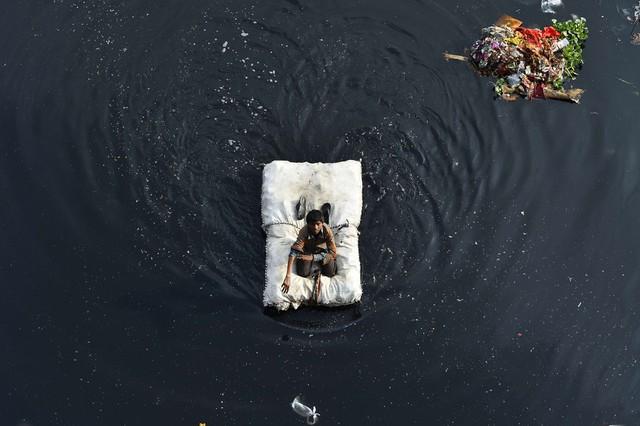 Cậu bé sử dụng bè tạm để di chuyển trên sông Yamuna ở New Delhi, Ấn Độ.
