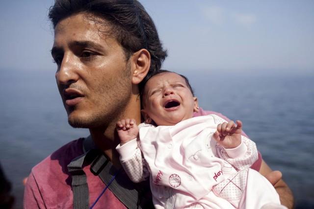 Người di cư Syria bế con gái nhỏ một tháng tuổi sau khi tới đảo Lesbos, Hi Lạp.