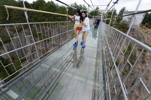 Du khách thích thú đi trên cây cầu treo với sàn bằng kính trong suốt tại tỉnh Hồ Nam, Trung Quốc.