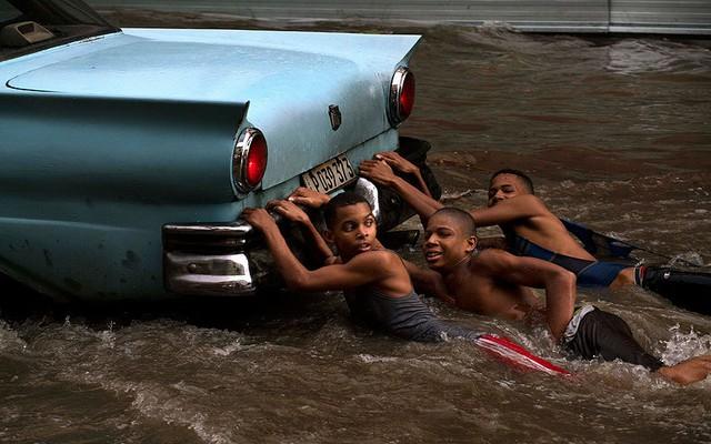 Các cậu bé bám vào sau một chiếc ô tô di chuyển trên đường phố ngập lụt ở Havana, Cuba.