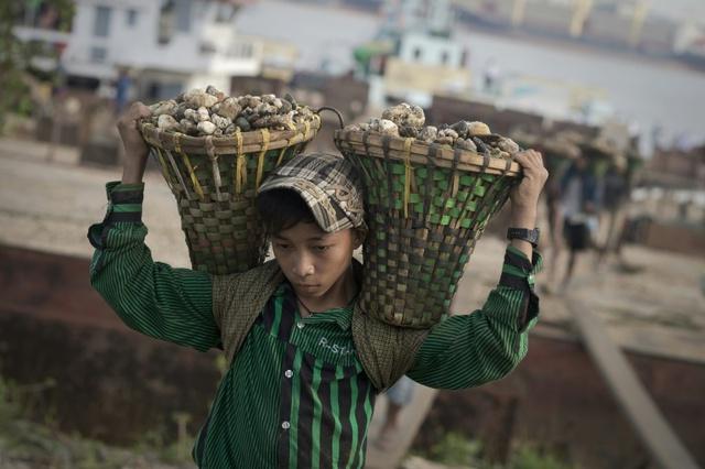 Cậu bé khuân đá từ một chiếc thuyền ở Dala, Myanmar.