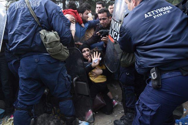 Người phụ nữ cố gắng bảo vệ con gái mình khi người di cư đụng độ với cảnh sát Hi Lạp tạo ngôi làng Idomeni giáp biên giới với Macedonia.