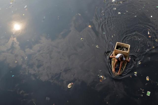 Người phụ nữ chèo chiếc bè tạm để nhặt rác trên dòng sông ô nhiễm tại thành phố Navotas, Philippines.