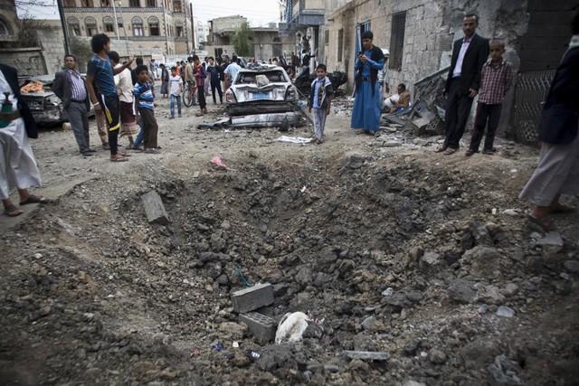 Mọi người đứng xung quanh một hố bom lớn sau đợt không kích của liên minh Ả-rập nhằm vào thành phố Sanaa, Yemen.