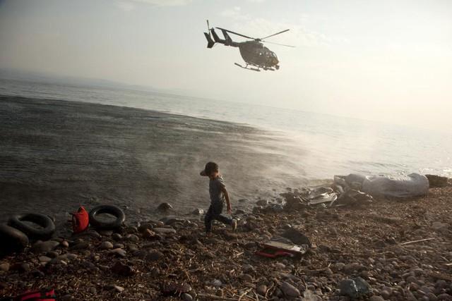 Máy bay trực thăng Frontex tuần tra trên đầu một cậu bé tị nạn người Syria vừa cập bến vào bãi biển trên đảo Lesbos, Hi Lạp.