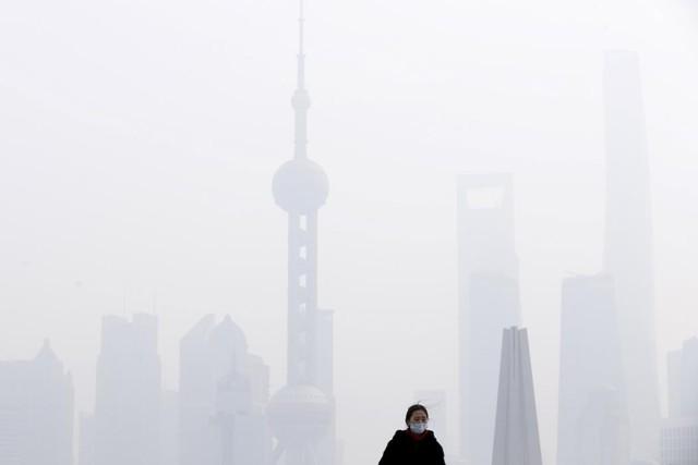 Người phụ nữ đeo khẩu trang đứng trên cây cầu trong bầu không khí ô nhiễm trước trung tâm tài chính Phố Đông ở Thượng Hải, Trung Quốc.