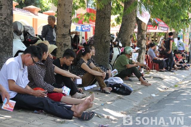 Trong khi các thí sinh đang làm thủ tục dự thi, phụ huynh ngồi bên ngoài tranh thủ tìm kiếm các bóng mát gốc cây để tránh nắng.