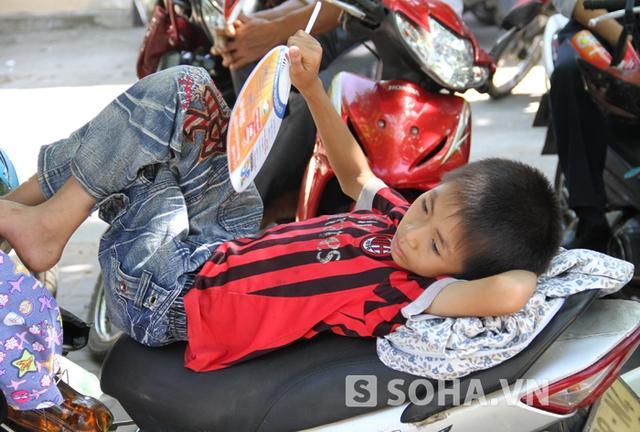 Em bé này theo mẹ đưa anh chị đi thi cũng tranh thủ nằm trên yên xe để chờ hết giờ làm bài.