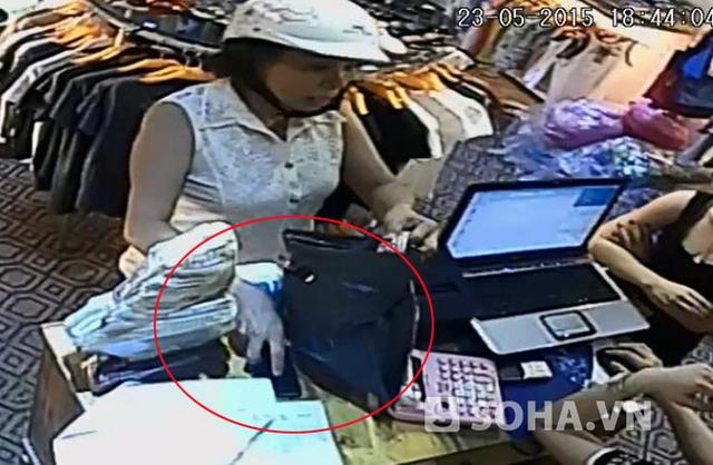 Cầm lấy túi đựng quần áo nhân viên đưa cho, nữ hành khách cố tình che chiếc iPhone 5 của nhân viên để giữa bàn.