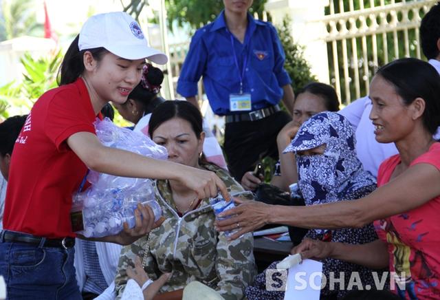 Để giảm bớt cái nắng nóng, các tình nguyện viên đưa nước đi phát cho các phụ huynh.
