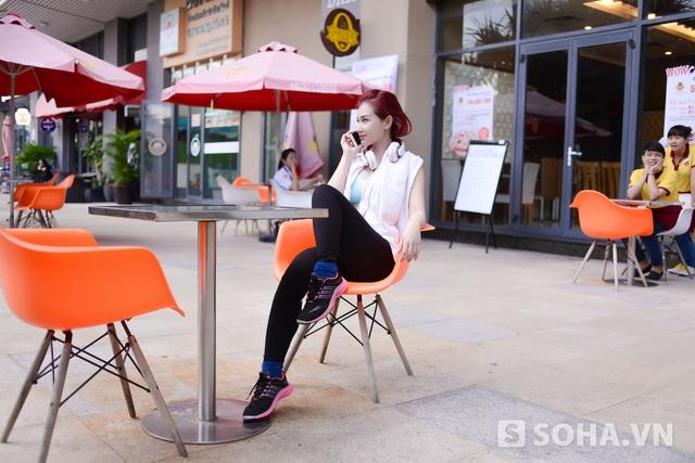Xong các bài tập, cô ngồi nghỉ mệt ở một quán cafe dưới chân tòa nhà. Phía sau Quỳnh Chi là hai nữ nhân viên của quán. Vì thấy cô nên họ lập tức di chuyển từ phía trong ra ngoài để ngắm người nổi tiếng.