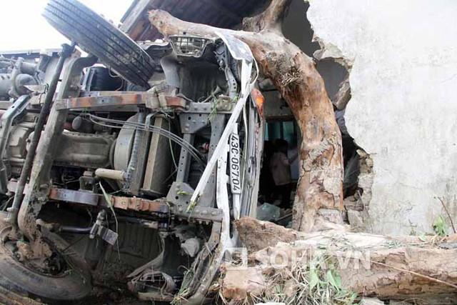 Đầu chiếc xe tải găm chặt vào cây sung trước khi lao tiếp đâm sập 1 góc nhà.