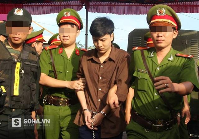 Bị cáo Dương cúi mặt khi được đưa vào khu vực xét xử rồi khi vô tình lướt mắt qua di ảnh 6 nạn nhân, Dương bật khóc