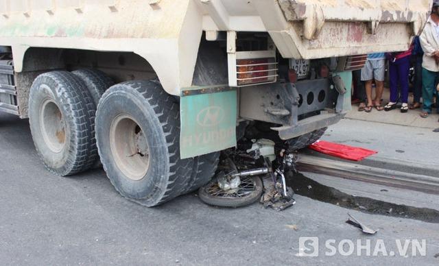 Xe máy nạn nhân cũng bị biến dạng và dính vào gầm xe ben