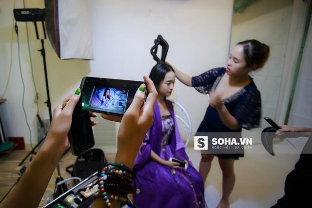 Một cô gái trong ekip đang chọn lựa và chỉnh trang đầu tóc cho Thúy Vi