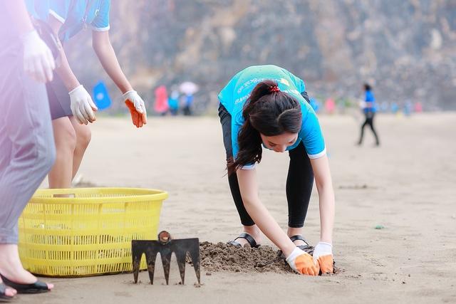 Gặp ca khó, người đẹp không thể dùng dụng cụ mà phải tự tay kéo rác lên khỏi bãi cát.