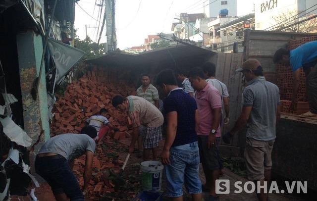Vụ va chạm khiến chiếc xe tải bị lật, hàng ngàn viên gạch rơi xuống đường