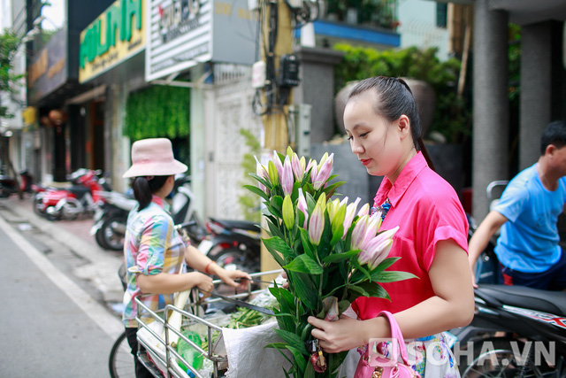 Đi chợ xong, chị di chuyển về nhà. Đang đi đường, người đẹp bỗng nhiên dừng lại. Hóa ra chị nhìn thấy một gánh hoa đẹp nên quyết định dừng xe để mua. Tôi hay mua hoa về cắm vì chồng thích hoa, chị cười rạng rỡ.