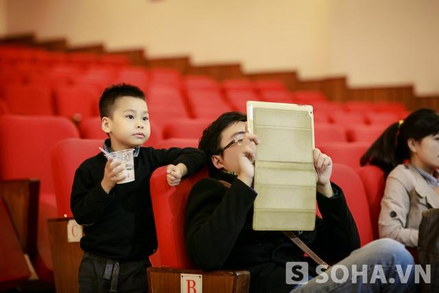 Trong khi mẹ tập luyện trên sân khấu, bé Khang ở dưới khán đài, chăm chú theo dõi từng động tác, từng lời hát của mẹ. Cậu bé đã rất quen với những buổi chạy show và đi tập cùng mẹ.