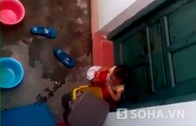 Hình ảnh cháu bé nhặt rác ăn do bị nhốt ở ngoài cửa (ảnh cắt từ clip)