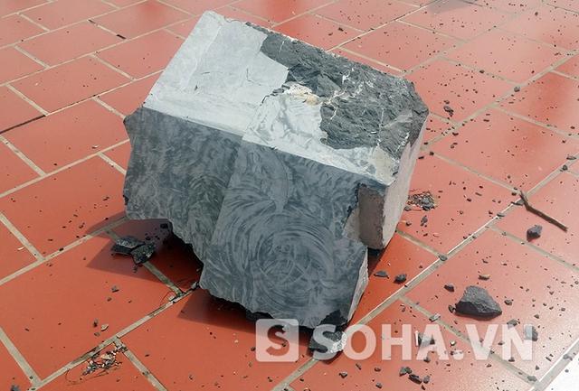 Tảng đá lớn từ bức tượng bị rơi xuống nền sân gạch