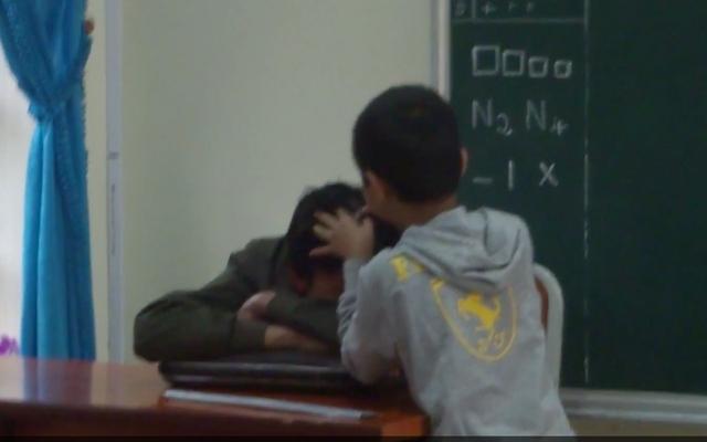 Hình ảnh thầy nằm gục trên bục giảng để trò nhổ tóc bạc (Ảnh cắt từ video clip)