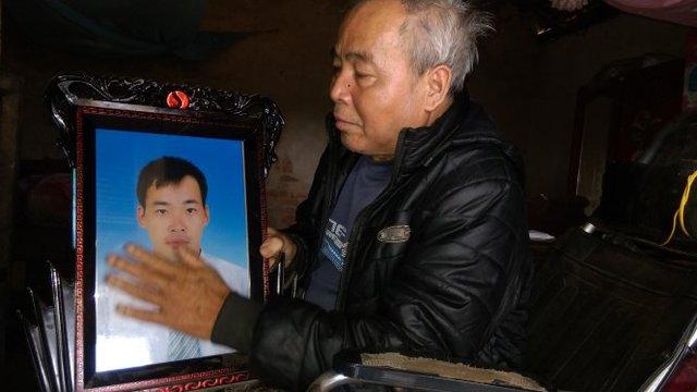 Ông Lê Văn Đường, 68 tuổi, ngồi trên xe lăn ôm di ảnh con trai chết bên Angola - Ảnh: Văn Định