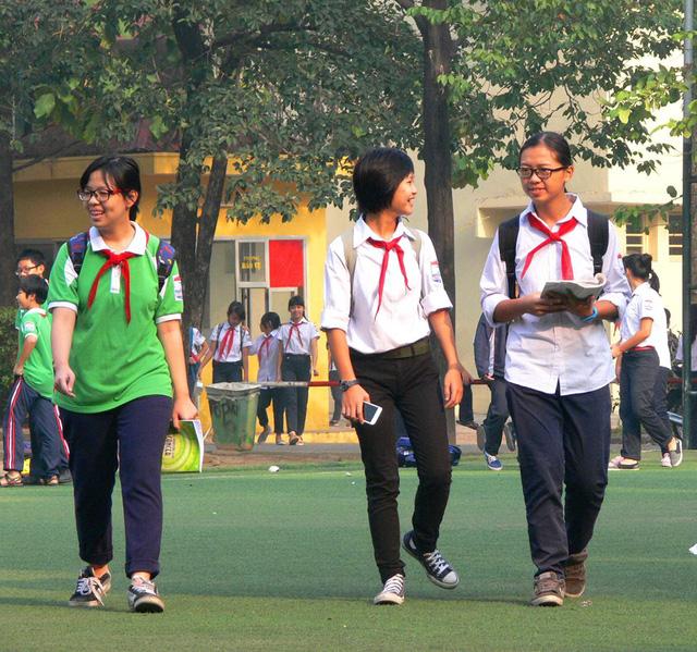 Bức ảnh bé Kiến (giữa) đeo khăn đỏ đi lại giữa sân trường