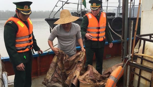 Cán bộ biên phòng của Việt Nam kiểm tra số lượng dầu không rõ nguồn gốc trên tàu của Trung Quốc - Ảnh: Hải đội 2 cung cấp