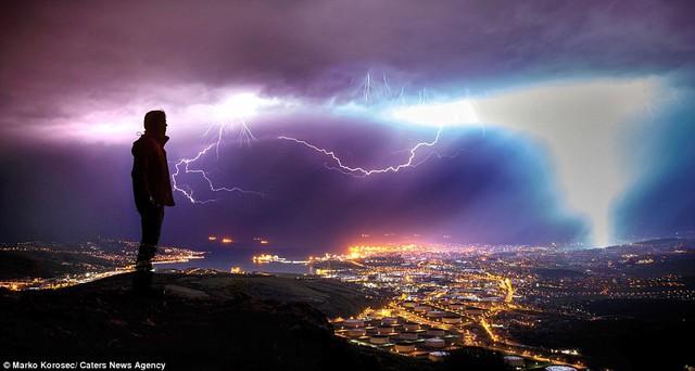 Nhiếp ảnh gia Marko Korosec đứng trên núi nhìn xuống thành phố Trieste, phía đông bắc Italia, trong lúc sấm sét ngập trời.