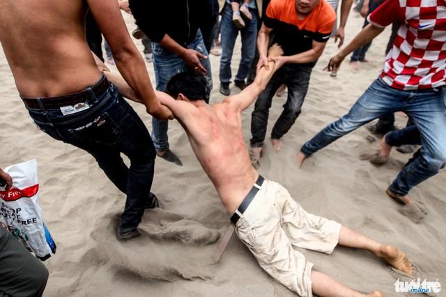 Thanh niên này bị ngất xỉu đang được đồng đội kéo ra khỏi đám đông hỗn loạn - Ảnh: Nguyễn Khánh