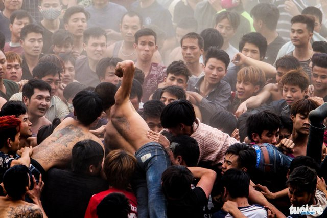 Một người đàn ông vung nắm đấm vào đám đông trong khi tranh giành phết - Ảnh: Nguyễn Khánh
