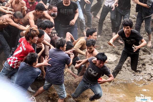 Một thanh niên cầm được quả phết cố gắng thoát khỏi đám đông và rơi vào vũng nước - Ảnh: Nguyễn Khánh
