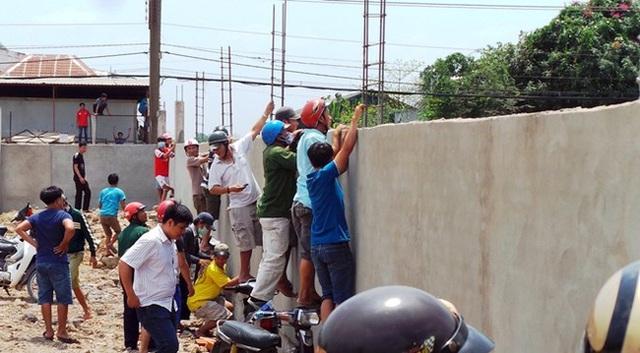 Một số người trèo lên tường của công trình bên cạnh nhìn vào hiện trường xác người bị chết cháy ở huyện Hóc Môn (TP HCM) sáng 24/3/2015, khiến lực lượng dân phòng vất vả giải tán đám đông - (Ảnh: Zing.vn)