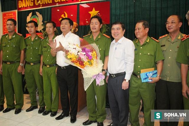 Bí thư Thành ủy Đinh La Thăng và Chủ tịch UBND TP.HCM Nguyễn Thành Phong tặng hoa và quà cho tập thể công an quận 1